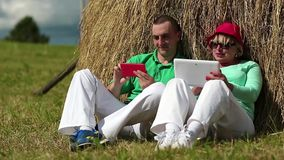 Man with red smartphone and woman with Tablet-PC sits near a haystack stock footage