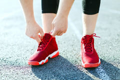 Man in red sneakers. Sport concept, red sneakers for running. Man tightening lacings on his sneakers, no face. Legs in professional sport shoes. Outdoors Stock Images