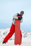 Man with red snowboard. Pretty man with red snowboard in red pants stock photo