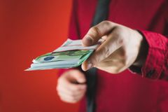 man in red suit holds out a wad of money in his hand on red background royalty free stock photos