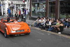 The man in red sunglasses is riding in a small vintage red car. The crowd looks at him. Bricklane Stock Photos