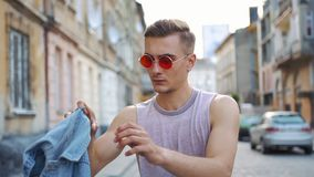 Man in red sunglasses takes on his jeans waistcoat walking along the street stock video