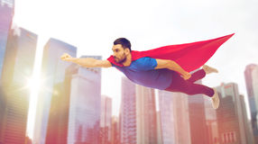 Man in red superhero cape flying over city Stock Image