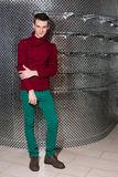 A man in a red sweater and green jeans Stock Image