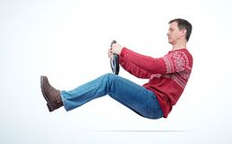 Man in red sweater jeans and boots drives a car with a steering wheel, on light background stock photo