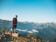 Man in Red Sweatshirt and Black Shorts Standing on Large Brown Rock on Top of a Mountain royalty free stock photo