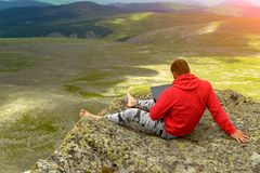 A man in a red sweatshirt sits on a rock on a mountainside stock photo