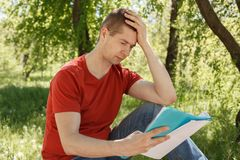 The man in a red t-shirt and jeans in the park Stock Photos