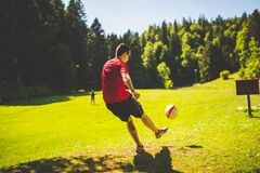 Man in Red T Shirt Playing Soccer during Daytime Royalty Free Stock Photos