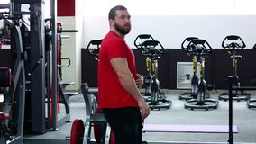 A man in a red T-shirt walks past the simulators.  stock footage