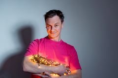Man in red t-shirt with a yellow glowing garland of light bulbs stock photo