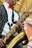 A closeup is masculine, playing on a gold saxophone. A man with a red tie is playing the saxophone. A close-up is masculine, playing on a gold saxophone Royalty Free Stock Photo