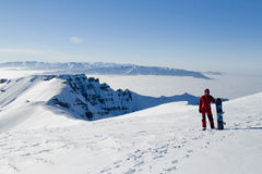 Man in red on the top of the mountains. Young man with snowboard in Bucegi mountains, Romania Stock Image