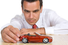 Man with red toy car. Businessman playing with a red toy car - isolated royalty free stock images