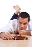 Man with red toy car. Businessman laying on the floor playing with a red toy car - isolated Royalty Free Stock Photo