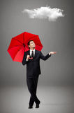 Man with red umbrella checks the rain. Palming up man with opened umbrella checks the rain and looks at the cloud overhead, isolated on grey Royalty Free Stock Photography