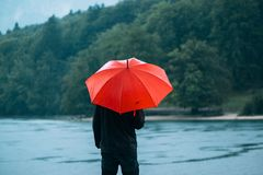 Man with red umbrella contemplates on rain Royalty Free Stock Photo