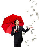 Man with red umbrella looks at falling money. Palming up man with opened umbrella looking at falling money, isolated on white. Concept of profit and successful Royalty Free Stock Photos