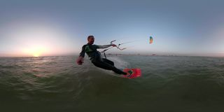 A man on a red wakeboard is engaged in kitesurfing and is holding a selfie stick. 360 degrees, a man in a diving suit skates to the sea in the morning stock video