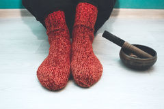 Man in a red woolen socks with a singing bowl Stock Photos