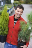 Man in red zip top shopping in garden centre, carrying two pot plants, smiling, portrait Royalty Free Stock Images