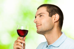 Man with redwine. Smiling man with red wine, outdoors Royalty Free Stock Photo