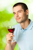 Man with redwine. Smiling man with red wine, outdoors Royalty Free Stock Images