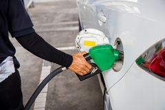 Man Refill and filling Oil Gas Fuel at station.Gas station - refueling.To fill the machine with fuel. Car fill with gasoline at a royalty free stock image
