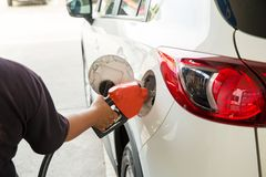Man Refill and filling Oil Gas Fuel at station.Gas station - refueling.To fill the machine with fuel. Car fill with gasoline at a stock photography