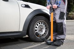 A man is refilling a car wheel Stock Image