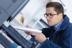 Man refilling photocopier paper tray. Photocopier Royalty Free Stock Image