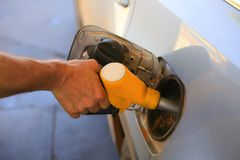 Man refills car, holds a filling gun in his hand. Hand close-up royalty free stock images