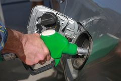Man refills car, holds a filling gun in his hand. Hand close-up stock photo