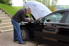 A man refills windscreen wiping water on a car Stock Images