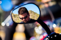 Man Reflected in Motorcycle Rearview Mirror. A man standing in front of an Arizona desert mountain is reflected in the rearview mirror of a motorcycle. He is Stock Photography