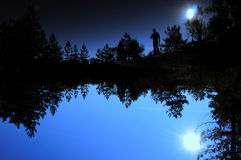 Man reflecting. Silouette of a man reflecting on a mountain lake stock photography