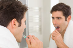 Man with reflection brushing teeth in the bathroom Royalty Free Stock Photos