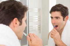 Man with reflection brushing teeth in the bathroom Stock Photography