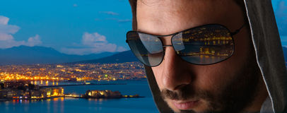 Man with the reflection of the city of Naples in the sunglasses. Stock Image