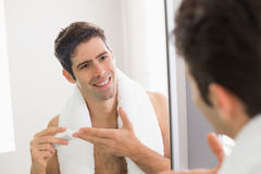 Man with reflection putting moisturizer on his face Royalty Free Stock Photography