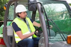 Man in reflective clothing operating heavy equipment in construction. Site Royalty Free Stock Image