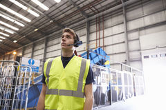 Man with reflective vest and headset standing in a warehouse Royalty Free Stock Photo