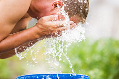 A man refreshes himself with a splash of water Stock Photography