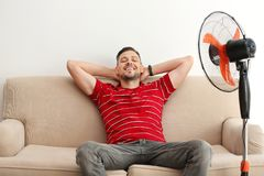 Man refreshing from heat in front of fan. At home stock image