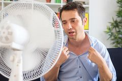 Free Man Refreshing With Electric Fan Against Summer Heat Wave Royalty Free Stock Photography - 121388977