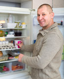Man and refrigerator. Man indoors taking food from refrigerator Stock Photo