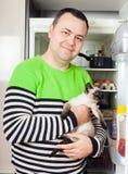 Man at refrigerator with kitten. Man at open refrigerator with kitten in arms stock images