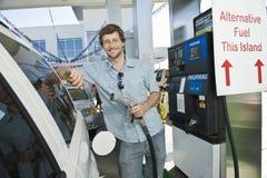 Man Refueling Car At Natural Gas Station. Portrait of smiling man refueling cropped car at natural gas station Royalty Free Stock Photos