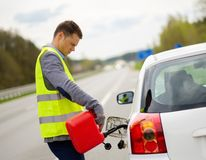 Man refuelling car on a roadside Stock Photo