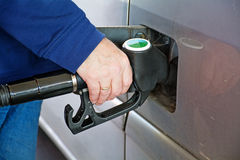 Man refuels his car in spite of high fuel-prices. Male hand holding gasoline pump into the tank of a car stock photos
